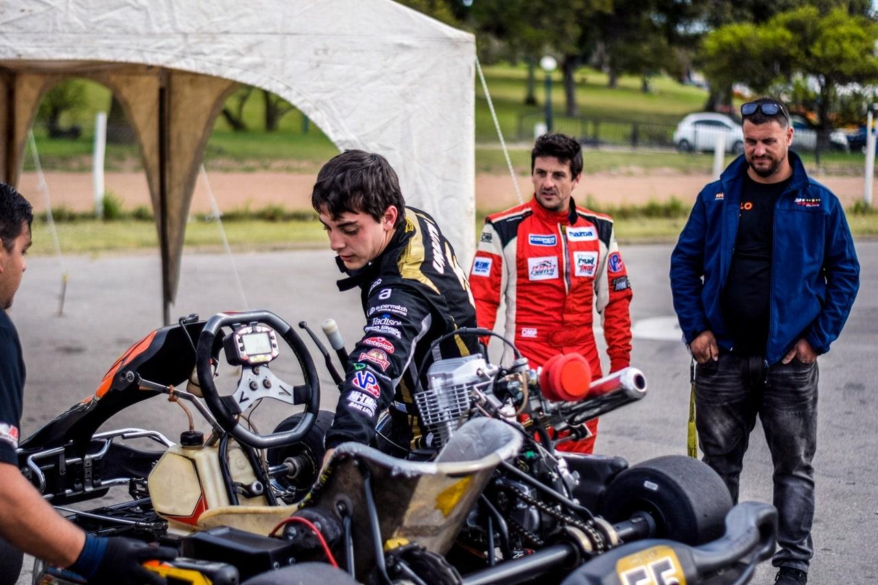 Go kart racers fixing vehicle