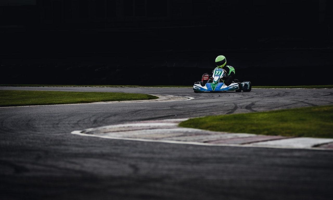 Man in green helmet riding go kart
