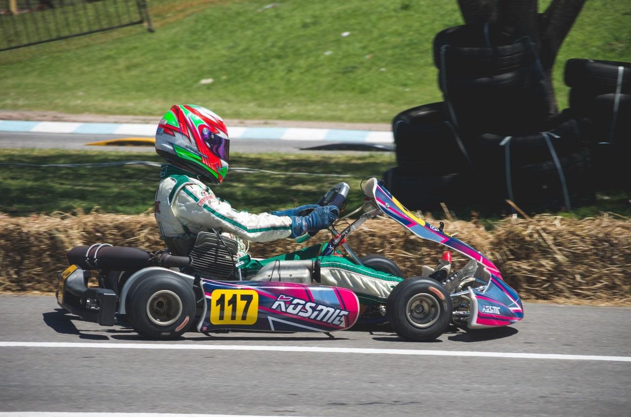 Man in racing suit riding go kart